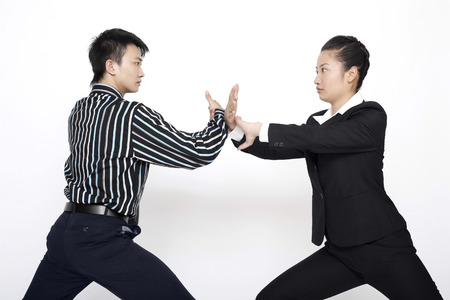 practising: Businessman and businesswoman practising martial arts LANG_EVOIMAGES