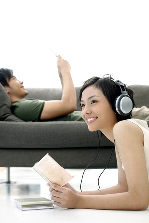 laying forward: Woman listening to music, man text messaging in the background