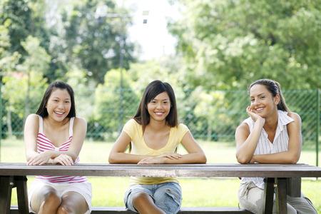 Three women sitting at a park table, looking at camera