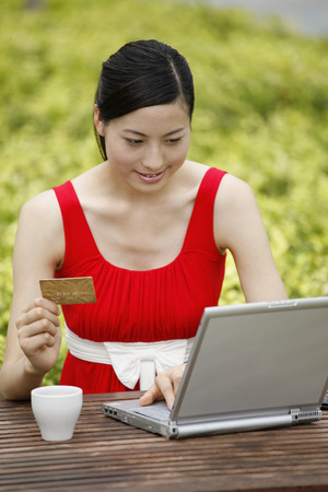 money matters: Woman with credit card using laptop