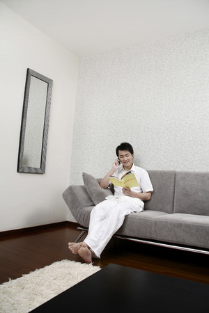 full grown: Man talking on the mobile phone while reading book