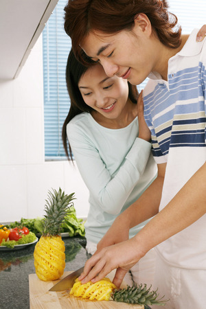 two persons only: Man cutting pineapple, woman watching LANG_EVOIMAGES