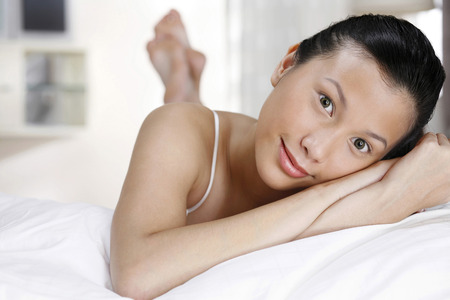 full grown: Woman lying forward on the bed, smiling at the camera LANG_EVOIMAGES