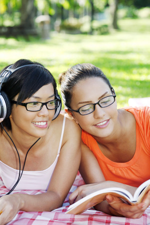 Woman reading book while her friend is listening to music on the headphones LANG_EVOIMAGES