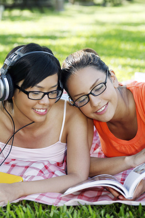 revision book: Woman reading book while her friend is listening to music using headphones LANG_EVOIMAGES