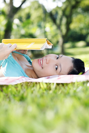 woman lying down: Woman lying down holding a book, looking at camera