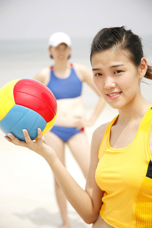 Woman holding volleyball, another woman in the background