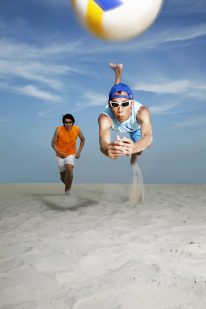 two persons only: Man diving to hit volleyball, man running in the background LANG_EVOIMAGES
