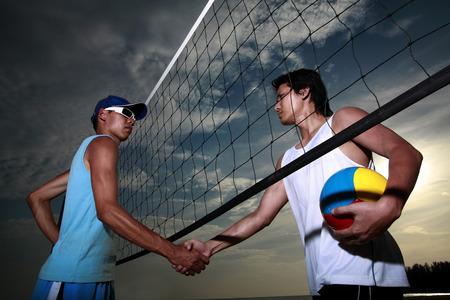 men shaking hands: Men shaking hands after a volleyball match