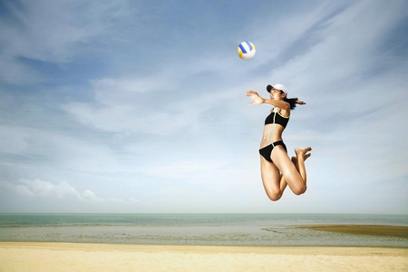 Woman reaching up to hit volleyball