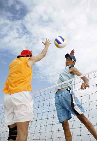two persons only: Men playing beach volleyball