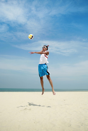 reaching up: Man reaching up to hit volleyball