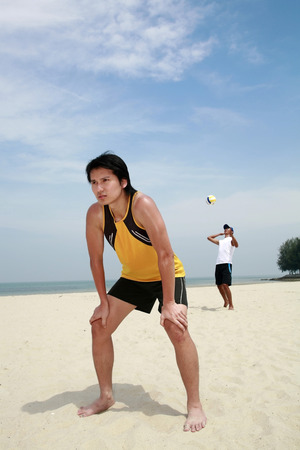 two persons only: Men playing volleyball on beach