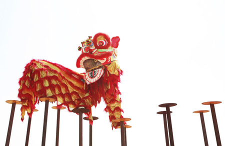 Performers in lion costume jumping from one stilt to the other 免版税图像