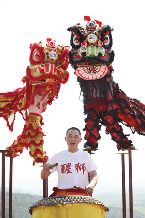 chinese drum: Performers in lion costumes standing on stilts, man playing chinese drum LANG_EVOIMAGES