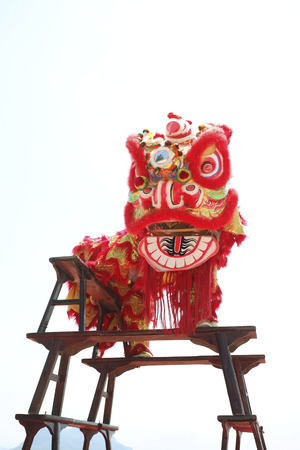 standing lion: Performers in lion costume standing on stacked benches
