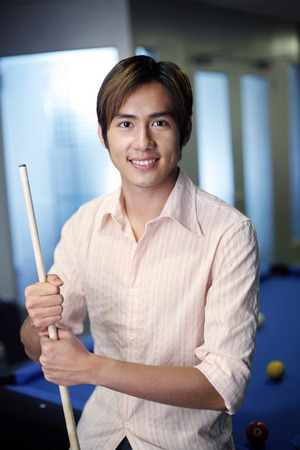 cue stick: Man with cue stick smiling at the camera LANG_EVOIMAGES