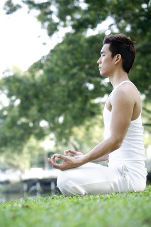 man meditating: Man meditating in the park