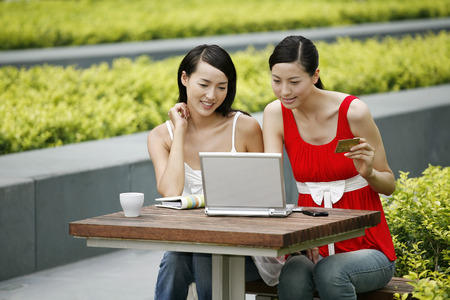 money matters: Woman with credit card using laptop, friend watching LANG_EVOIMAGES