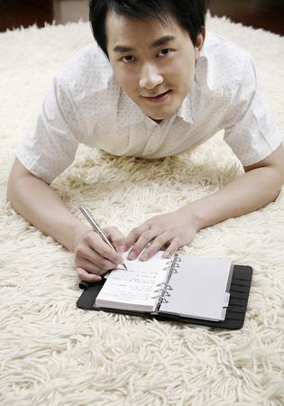 lying forward: Man lying forward on floor carpet, writing on organizer LANG_EVOIMAGES