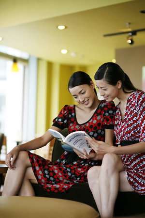 reading magazine: Women reading magazine together