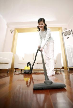 vacuuming: Woman vacuuming the living room