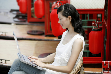 Woman using laptop on a boat