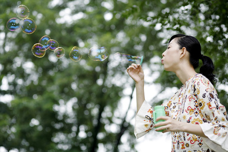 woman blowing: Woman blowing soap bubbles LANG_EVOIMAGES