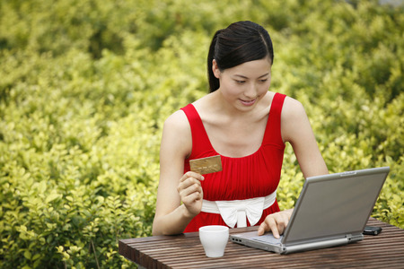 money matters: Woman holding credit card while using laptop