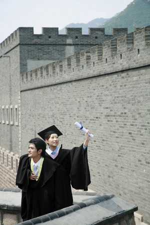 he is a traditional: Man and woman in graduation robes LANG_EVOIMAGES