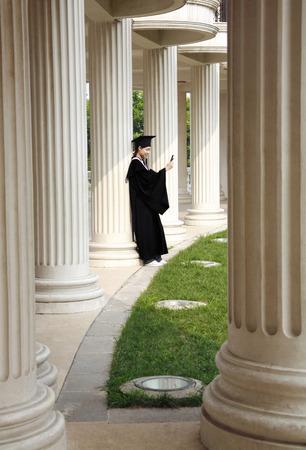 camera phone: Female graduate taking picture with camera phone