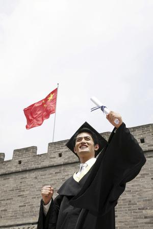 jubilating: Man in graduation robe holding scroll LANG_EVOIMAGES