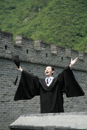 jubilating: Woman in graduation robe holding mortar board