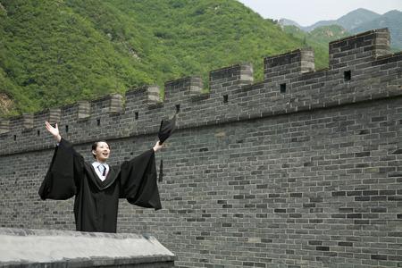 jubilating: Woman in graduation robe holding mortarboard