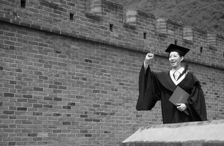 jubilating: Woman in graduation robe celebrating her success LANG_EVOIMAGES