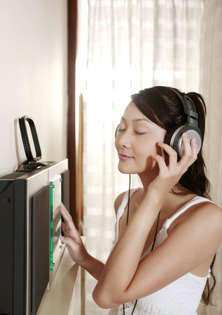 eyes closing: Woman closing her eyes while listening to music on the headphones