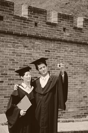 he is a traditional: Man and woman in graduation robes taking picture together