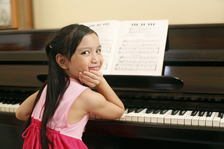 elementary age girl: Girl playing piano