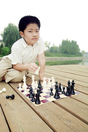 jugando ajedrez: Boy playing chess game by the lakeside LANG_EVOIMAGES