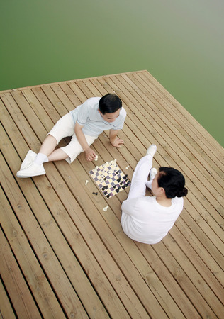 two persons only: Senior man and woman playing chess game by the lakeside LANG_EVOIMAGES