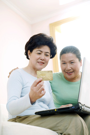 holding credit card: Woman holding credit card while using laptop, another woman watching