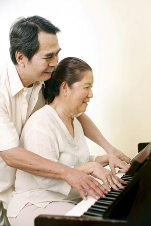 playing piano: Senior man and woman playing piano