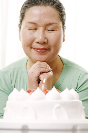 Woman making a wish in front of birthday cake
