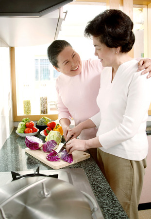 two persons only: Women cutting vegetables in the kitchen