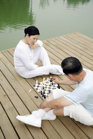 two persons only: Senior man and woman playing chess by the lakeside LANG_EVOIMAGES