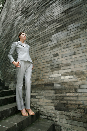 pensiveness: Businesswoman at stairway LANG_EVOIMAGES