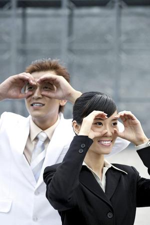 sensory perception: Business people making gestures as though looking through binoculars