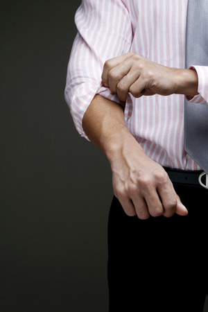 midsection: Businessman rolling up his sleeve