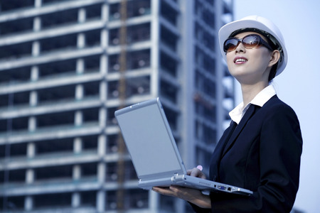 Businesswoman with laptop at construction site
