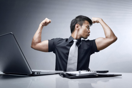 pouting: Businessman showing his muscles and pouting his mouth as though kissing his muscle
